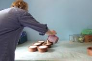 Patrice beim Befüllen der Tontöpfe mit Büffelmilch